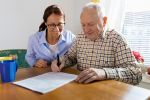 Caregiver and elderly man reading paperwork