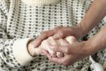 Caretaker holding older mans hand, reassurance of safety, vulnerable adult concept.